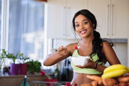 Female eating bowl of fruit