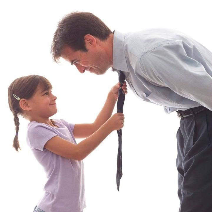 Young girl fixing dad's tie
