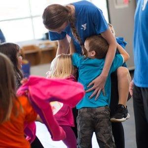 Kids hugging staff member