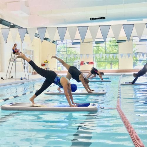 Fitness class on paddle board in pool