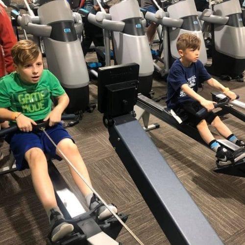 boys exercising on rowing machine