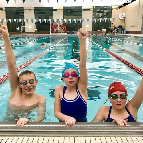 children posing with one arm raised in the pool